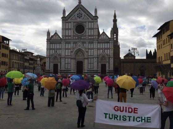 Guide in piazza Santa Croce senza turisti, con ombrelli e manuali d'arte